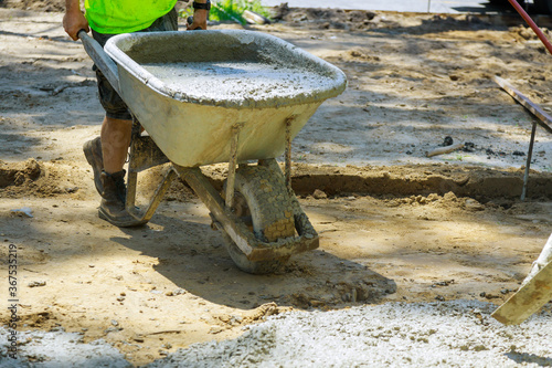 Canvas Print Construction worker pushing wheelbarrow with concrete at building