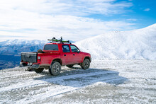 Red Pickup Truck On Road, Beautiful Winter Road Under Snow Mountains New Zealand.