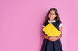 canvas print picture - A charming girl with long curly dark hair in a school uniform with a book in her hands on a pink background. Studio photo. Back to school.