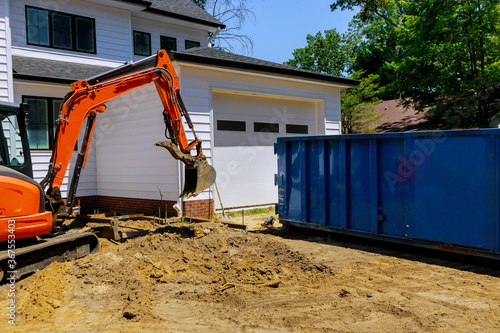 Obraz Mini excavator on construction site for working in trash container construction dumpsters - fototapety do salonu