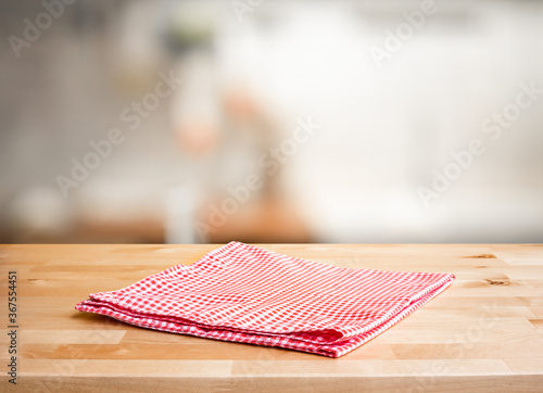 Obraz Red fabric,cloth on wood table top on blur kitchen counter (room)background - fototapety do salonu