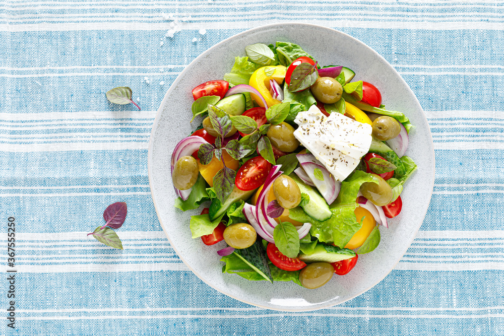 Fototapeta Greek salad. Fresh vegetable salad of cucumbers, tomatoes, olives, onion, bell pepper, feta cheese, lettuce and herbs and dressed with salt, pepper and olive oil. Popular greek Horiatiki salad
