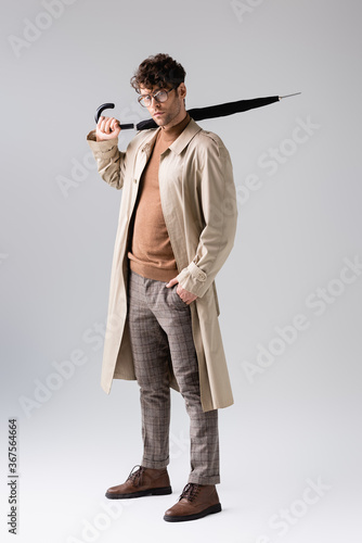 full length view of trendy man holding folded umbrella while looking at camera on grey