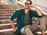 Fototapeta Na drzwi - Portrait of handsome smiling stylish hipster lambersexual model.Man dressed in green shirt. Fashion male sitting at the stairs on the street background in sunglasses