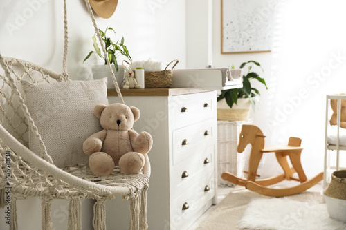 Obraz Stylish swing and changing table in baby room. Interior design - fototapety do salonu