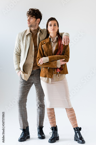 Full length view of stylish man with hand in pocket looking away while embracing attractive woman standing near on grey