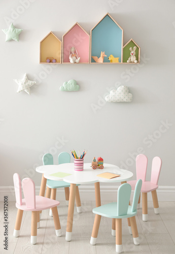 House shaped shelves and little table with chairs in children's room. Interior design