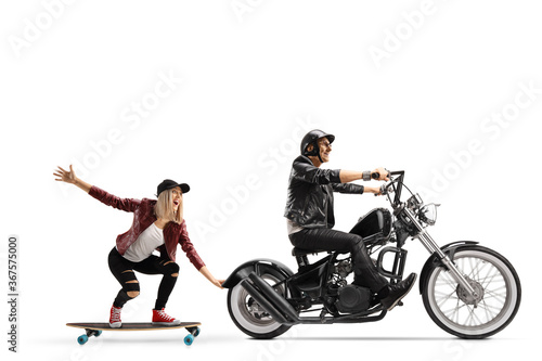 Photo Biker on a chopper pulling a young woman on a skateboard