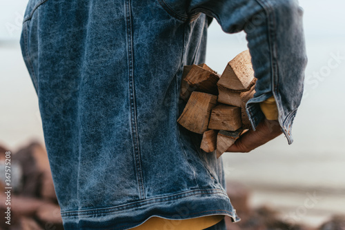 Photo cropped view of man in denim jacket holding firewood