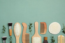 Flat Lay Composition With Modern Hair Combs And Brushes On Green Background. Space For Text