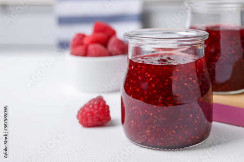 Obraz Delicious jam and fresh raspberries on white table, closeup. Space for text - fototapety do salonu