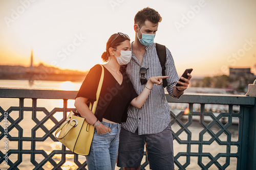 Fototapeta Young couple with protective face masks using smart phone on their vacation in Istanbul. obraz na płótnie
