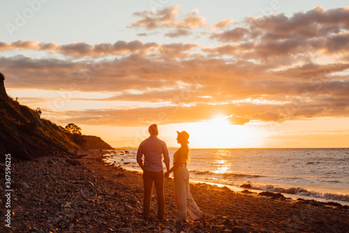 Fotografie, Obraz Young couple walking in sunset on the beach