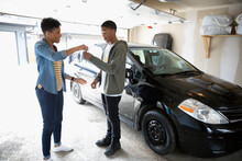 Mother Giving Car Keys To Teenage Son In Garage