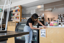 Young Woman Putting Safety Distance Poster On Cafe Counter