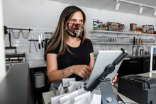 Young Woman Wearing Face Mask Working In Cafe
