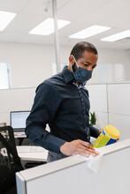 Man Wearing Facemask Sanitizing Office Partition