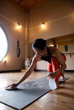 Woman Cleaning Yoga Mat In Stu...