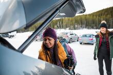 Woman Unloading Car In Snowy S...