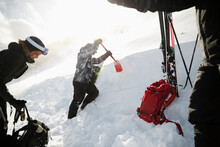 Skiers With Shovel Digging Sno...