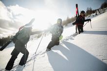 Snowboarder Helping Skier Clim...
