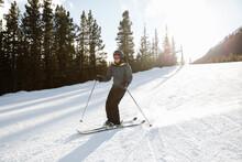 Man Downhill Skiing On Sunny Snowy Ski Slope