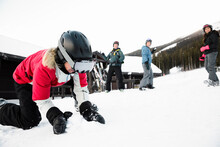 Female Skier Making Snowball In Snow