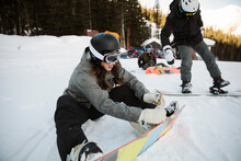 Female Snowboarder Clipping In...