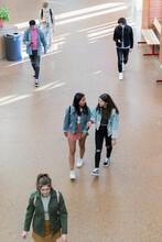 High School Girl Friends Talking And Walking In Corridor