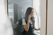 Woman Using Soundproof Phone Booth In Modern Office