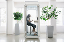 Woman Working In Office Phone Booth