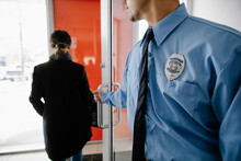 Security Guard Wearing Badge Opening Door