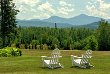 Inviting And Restful Scenic Vista In Whitefield, New Hampshire. White Lawn Chairs Overlooking Hillside Of Lush Evergreen Trees Framed By Distant Mountains In The White Mountains Presidential Range.