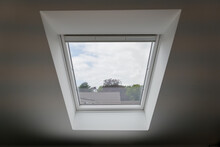 Interior View At Closing White Tilt Window Skylights At Attic And Defocused Of The Roof Of House.
