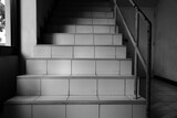 Low angle view of staircase in a building under sunlight, black and white image
