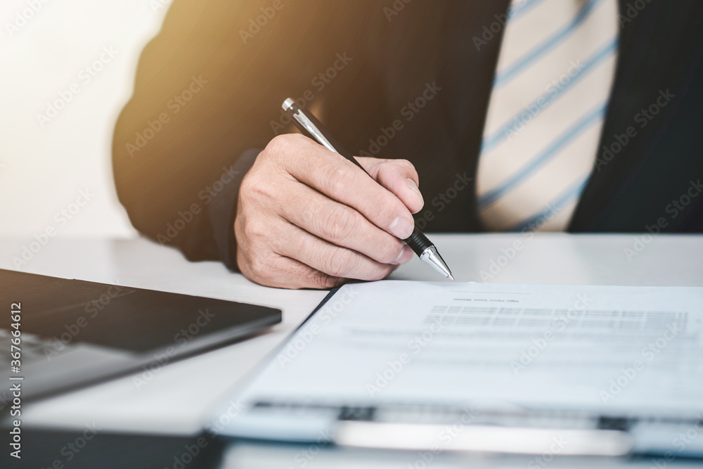 Fototapeta Young business man signing a last will and testament document in the office.