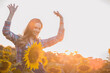 Beautiful, gorgeous female farmer cheering happily in the middle of a sunflower field during sunrise.