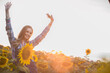 Beautiful, young, female farmer cheering happily in the middle of a sunflower field during sunrise.