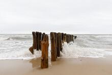 Wooden Poles As Wave Breaker On Island Sylt In Germany