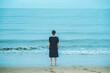 波打ち際に立つ日本人女性 後ろ姿 雨天