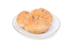 Three Small Croissants On A White Plate On A Blue Background.