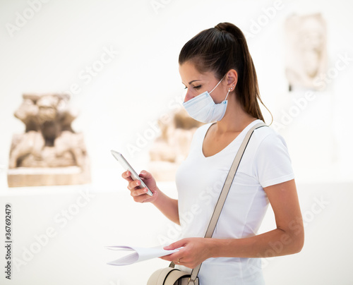Portrait of young female visitor in disposable face mask using phone in sculptur Fototapeta