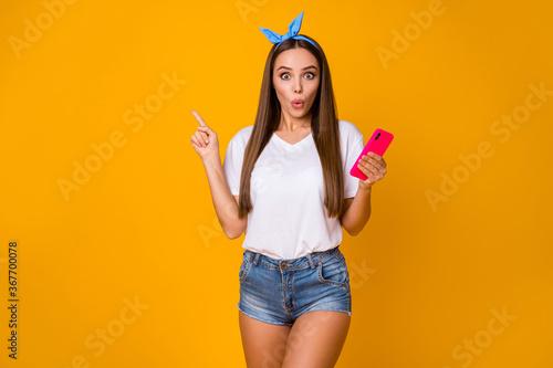 Obraz na plátně Astonished girl promoter use smartphone point index finger copyspace indicate in