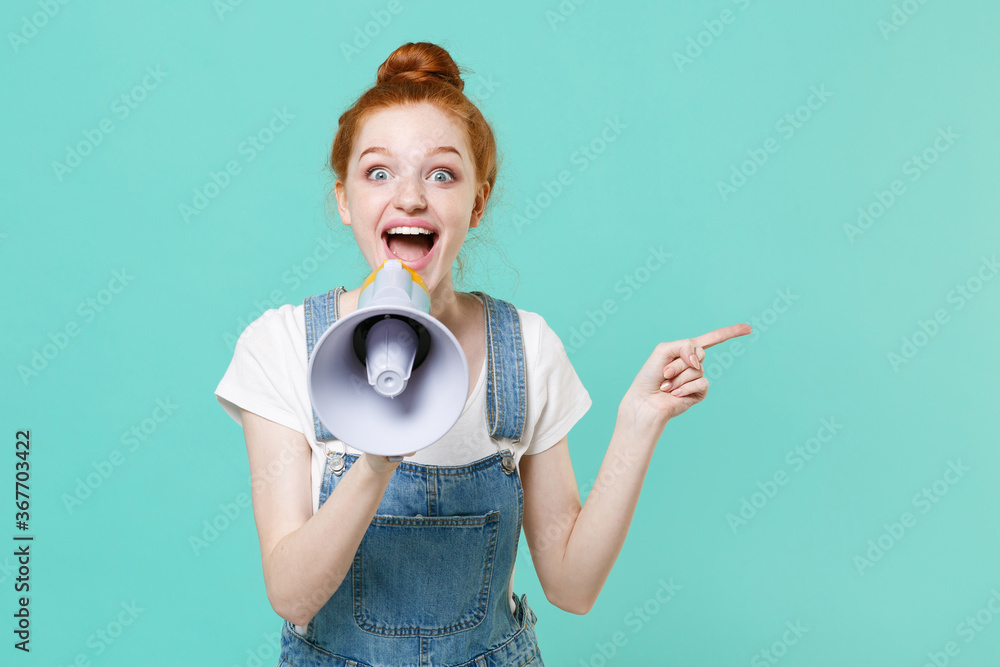 Fototapeta Excited young readhead girl in casual denim clothes posing isolated on blue turquoise background studio. People lifestyle concept. Mock up copy space. Scream in megaphone, pointing index finger aside.