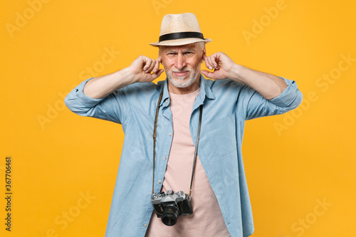 Displeased traveler tourist elderly gray-haired man in hat photo camera isolated on yellow background Fotobehang