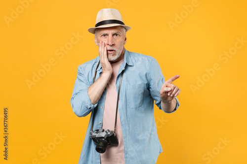 Fotografie, Obraz Shocked traveler tourist elderly gray-haired man in hat photo camera isolated on yellow background