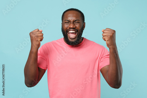 Joyful young african american man guy in casual pink t-shirt posing isolated on pastel blue background studio portrait. People emotions lifestyle concept. Mock up copy space. Doing winner gesture.