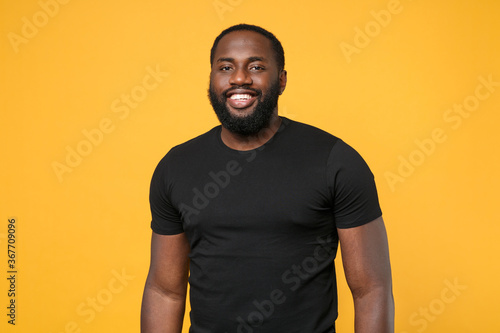 Obraz Smiling african american man guy football fan in casual black t-shirt isolated on yellow wall background studio portrait. People sincere emotions lifestyle concept. Mock up copy space. Looking camera. - fototapety do salonu