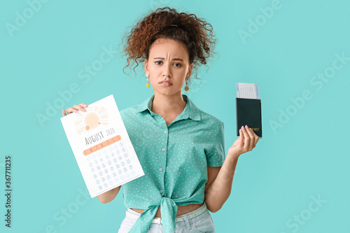 Tela Sad woman with calendar, passport and ticket on color background