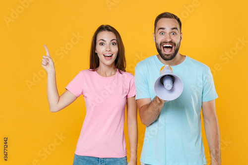 Excited young couple two friends guy girl in blue pink t-shirts posing isolated on yellow background. People lifestyle concept. Mock up copy space. Screaming in megaphone point index finger aside up.